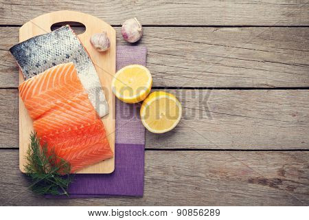 Salmon, spices and condiments on wooden table. Top view. Toned