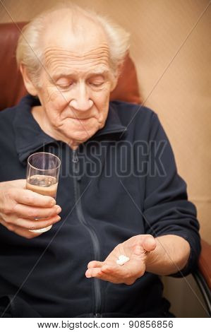 Old Man Holding A Glass Of Water And Pills