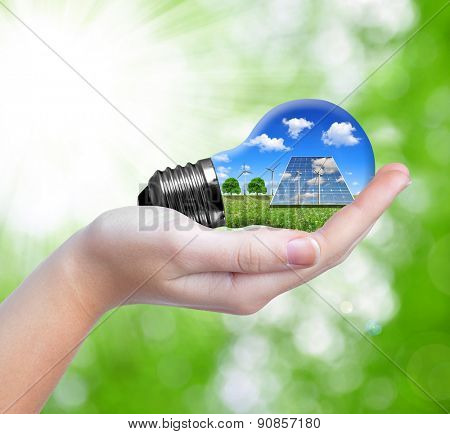 Hand holding eco light bulb on green background