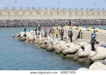 Jeju-do, Korea - April 08, 2015: Fishermen On A Breakwater