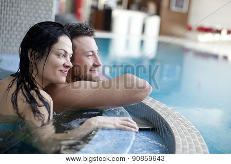 Couple relaxing in jacuzzi of spa center