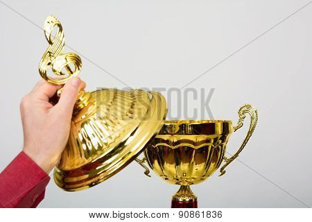 Hand Opens Lid Of Gold Cup