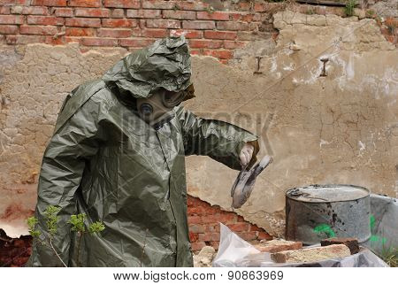 Man With Gas Mask And Green Military Clothes  Explores   Dead Bird After Chemical Disaster.