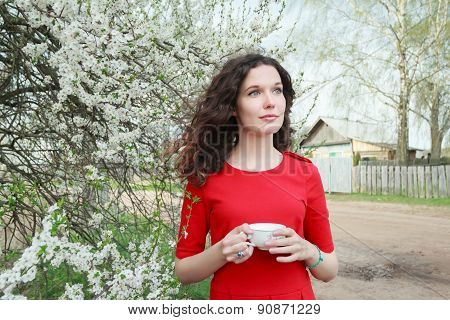 Daydreaming attractive brunette girl at spring fruit tree in bloom