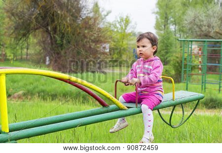 Little Cute Girl Sits On Seesaw In A Sunny Day
