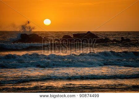 Sunset Above The Ocean From The Rocky Beach
