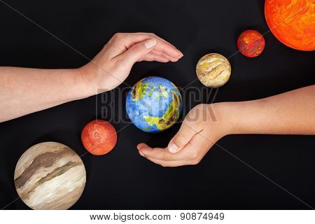 Concept of protecting Earth - with hands shielding our planet, on black background