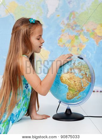 Young girl finding places on a globe - elementary school education concept