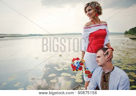 Wedding Beautiful Couple In Traditional Dress On The Dock