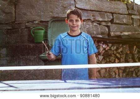 Portrait Of Young Smiling Boy Outside In Front Of Tennis Table