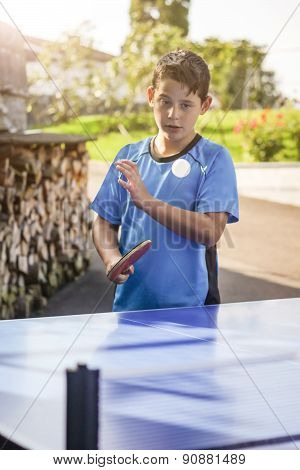 Portrait Of Young Boy Outside Who Hit The Ball In Front Of Tennis Table