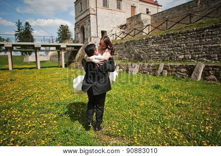 Wedding Couple Near Old Castle At The Field Of Dandelions