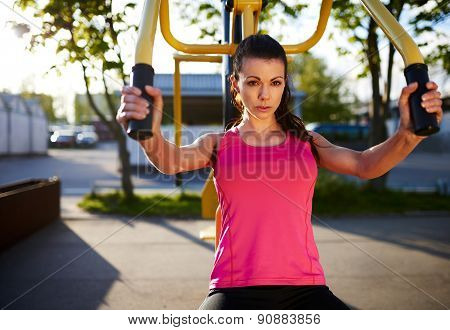 Upper Body View Of Woman Using Weights Machine.