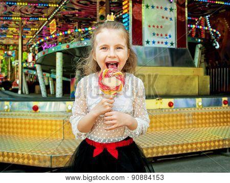 Cute Little Girl With Lollipop At Amusement Park