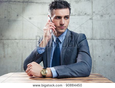 Businessman sitting at the table and talking on the phone over concrete wall and looking away