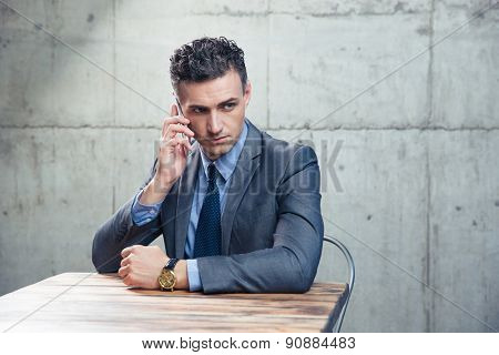 Pensive businessman sitting at the table and talking on the phone over concrete wall. Looking away