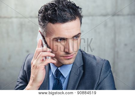 Closeup portrait of a confident businessman talking on the phone and looking away over concrete wall