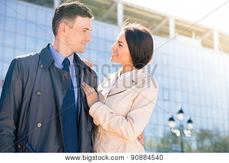 Happy couple standing outdoors and looking to each other with glass building on background