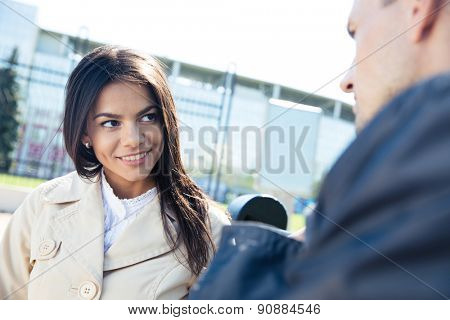 Portrait of smiling woman and man talking outdoors and looking at each other