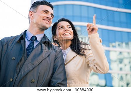 Happy couple looking up on something outdoors with glass building on background