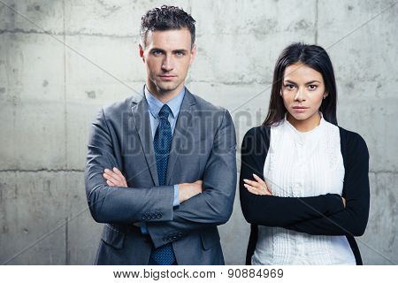 Businesswoman and businessman with arms folded standing over concrete wall and looking at camera
