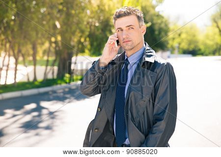 Thoughtful businessman in suit talking on the phone outdoors and looking away