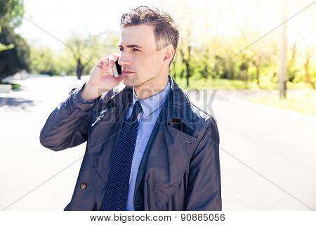 Confident businessman talking on the phone outdoors and looking away