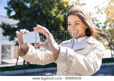 Smiling cute woman making photo on smartphone outdoors