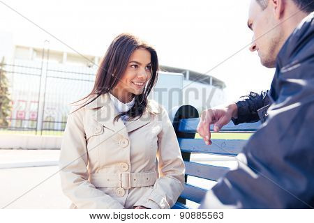 Happy woman talking with man outdoors. Sitting on the bench. Looking at each other