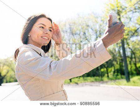 Smiling woman making selfie photo outdoors