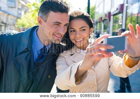 Smiling beautiful couple making selfie photo on smartphone outdoors in the city
