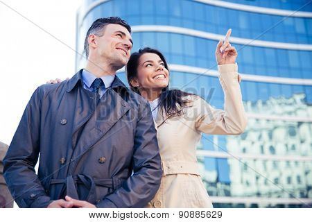 Smiling couple looking up on something outdoors with glass building on background