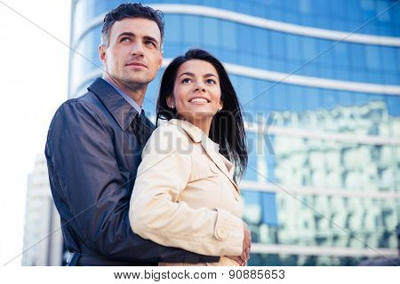 Smiling young couple hugging outdoors and looking away with glass building on background