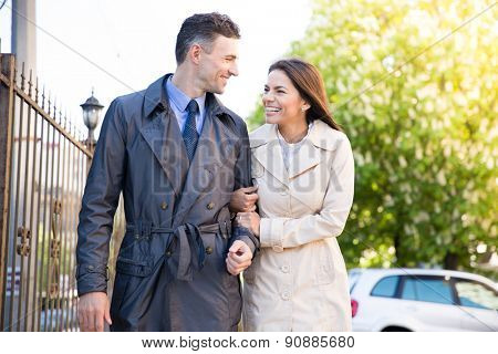 Smiling young couple walking and flirting outdoors