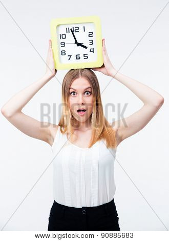 Surprised woman holding big clock isolated on a white background. Looking at camera