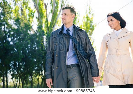 Happy beautiful couple walking outdoors and looking away