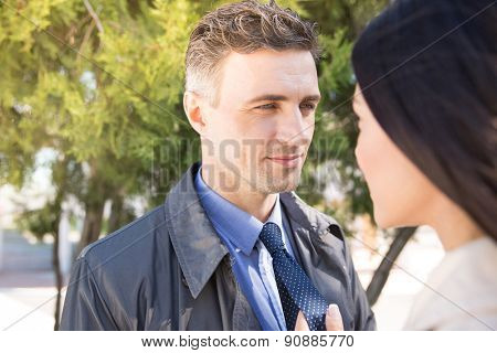 Portrait of a handsome man and woman looking at each other outdoors