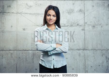 Portrait of a smiling businesswoman standing with arms folded over concrete wall and looking at camera