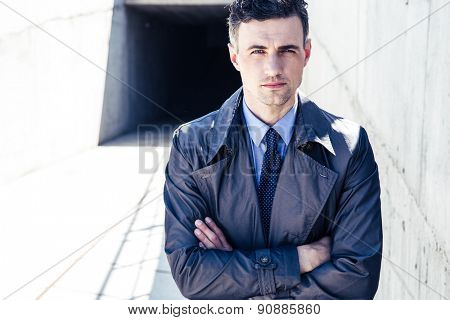 Portrait of a handsome businessman standing outdoors with arms folded and looking at camera