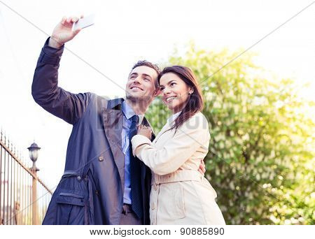 Happy young couple making selfie photo on smartphone outdoors