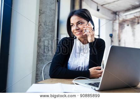 Happy businesswoman sitting at the table and talking on the phone in cafe. Looking away