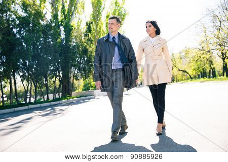 Full length portrait of a smiling couple walking outdoors