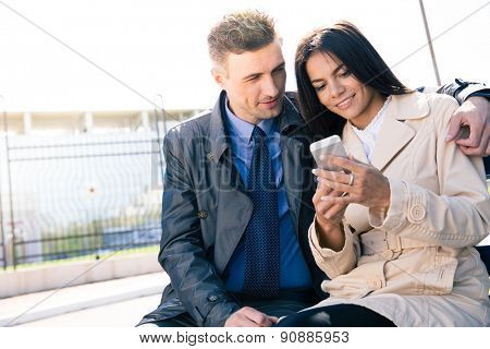 Happy couple using smartphone together outdoors