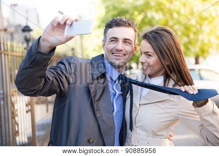 Smiling beautiful couple making selfie photo on smartphone outdoors