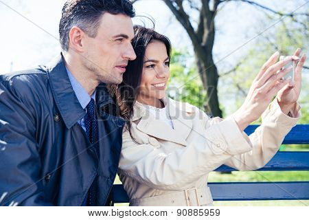 Cheerful couple making selfie photo on smartphone outdoors