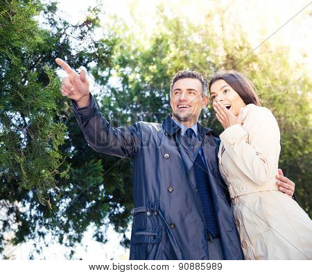 Portrait of a man pointing on something with happy woman in park