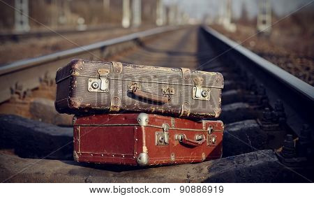 The Image Of Two Vintage Suitcases On Railway Tracks.
