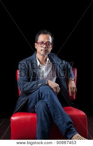 Portrait Face Of 45S Years Old Asian Man Sitting On Red Sofa In Dark Room With Studio Lighting Photo