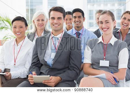 Smiling business people looking at camera during meeting in office