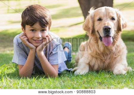 Little boy looking at camera with his dog in the park on a sunny day